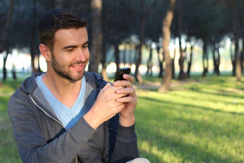 Het blije mannelijke texting in het park royalty-vrije stock afbeeldingen