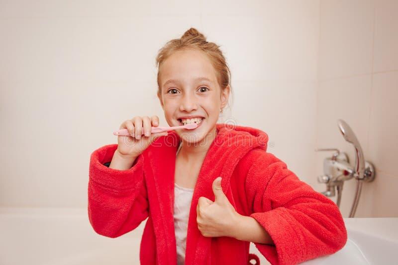 Het blije meisje borstelt tanden in een badkamers royalty-vrije stock foto