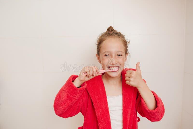 Het blije meisje borstelt tanden in een badkamers royalty-vrije stock foto's