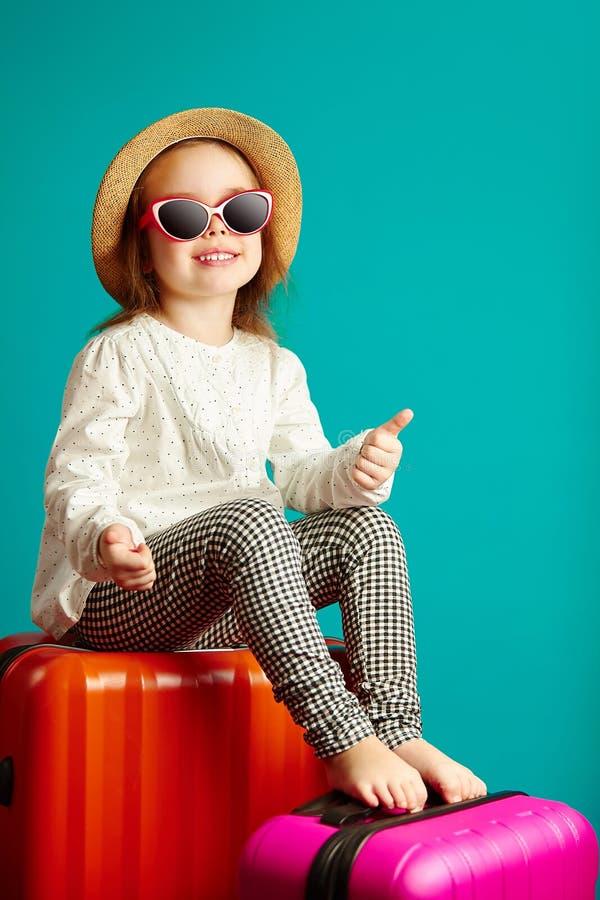 Het blije meisje gaat overhalen, zittend op koffers, die een strohoed dragen en de zonnebril, toont duimen, portret stock foto