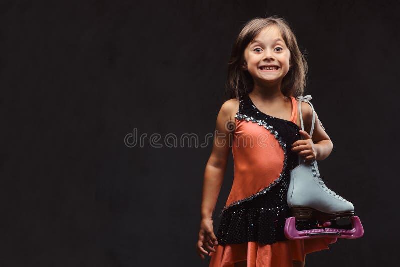 Het blije meisje gekleed in schaatserkleding houdt schaatsen Geïsoleerd op een donkere geweven achtergrond stock fotografie