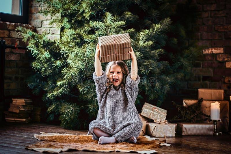 Het blije meisje met blonde krullend haar die een warme sweater dragen werpt op een giftdoos terwijl het zitten op een vloer naas stock afbeeldingen