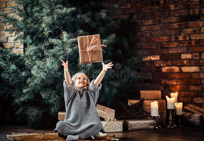 Het blije meisje met blonde krullend haar die een warme sweater dragen werpt op een giftdoos terwijl het zitten op een vloer naas royalty-vrije stock afbeeldingen