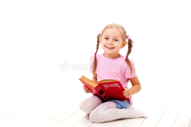 Het blije meisje met boeken zit op een witte vloer stock fotografie