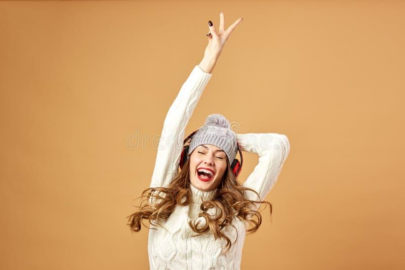 Het blije meisje in rode hoofdtelefoons gekleed in witte gebreide sweater en hoed heeft pret op een beige achtergrond in de studi stock fotografie