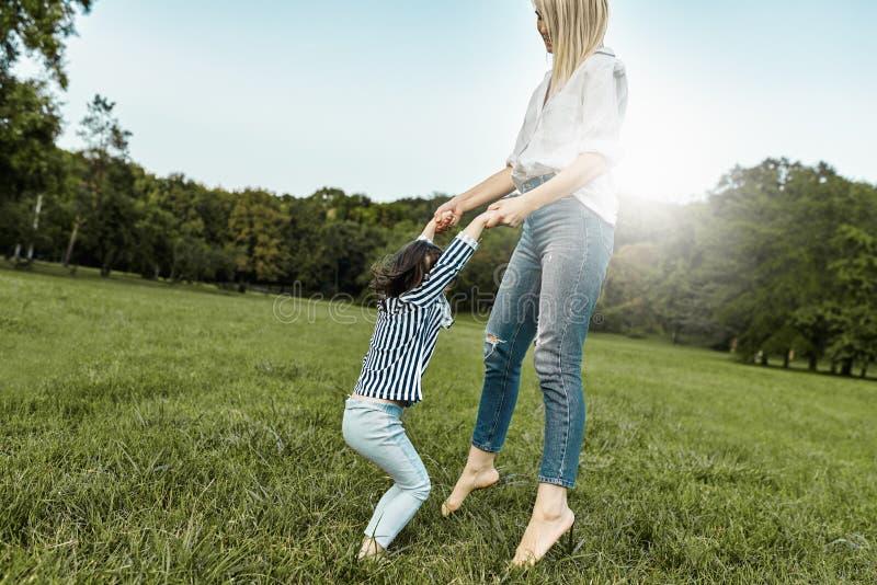 Het blije meisje spelen met haar moeder op groen gras Houdende van mooie vrouw en haar dochter het besteden tijd samen en stock foto