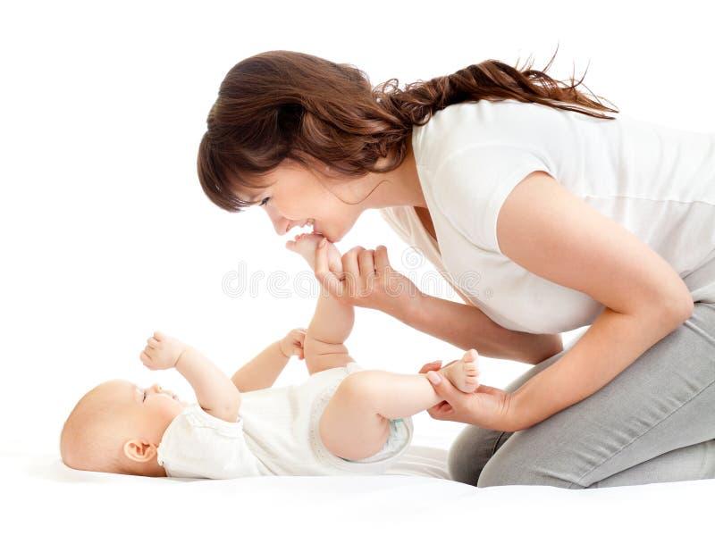 Het blije moeder spelen met haar babyzuigeling stock foto's