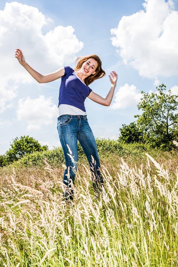 Het blije mooie jonge meisje springen, die in hoog droog gras dansen royalty-vrije stock foto
