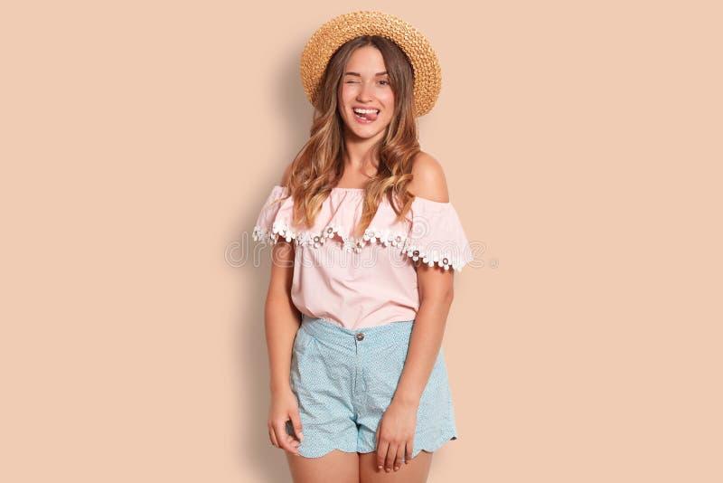 Het blije mooie wijfje met gelukkige uitdrukking, knipoogjesoog, toont tong, draagt strohoed, gekleed die in de zomerkleding, ove stock afbeelding