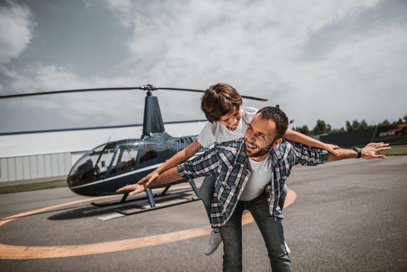 Het blije papa spelen met zoon dichtbij helikopter stock afbeeldingen