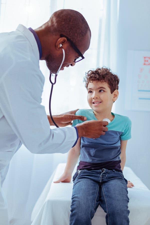 Het blije positieve arts genieten die met kinderen werken royalty-vrije stock fotografie