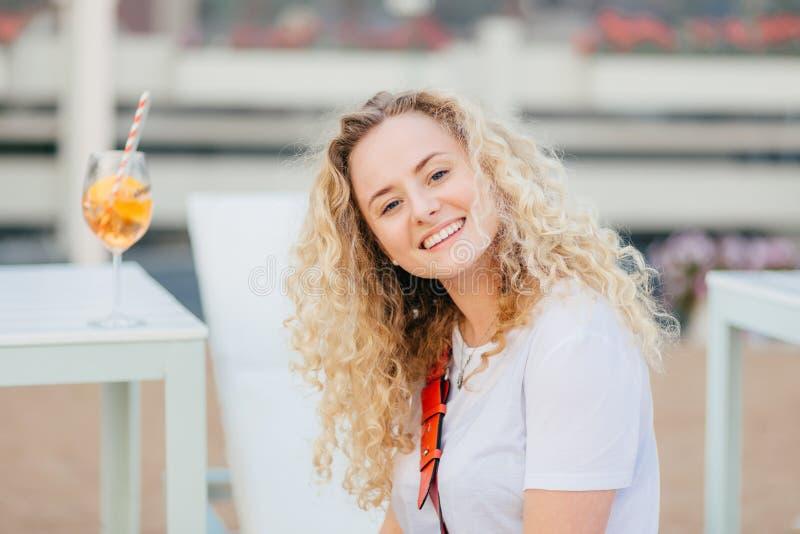 Het blije prettige kijken blondewijfje met golvend haar, heeft brede het glanzen glimlach, gekleed in vrijetijdskleding, rust in  royalty-vrije stock afbeeldingen