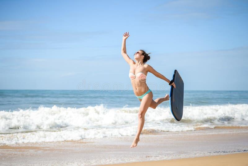 Het blije surfermeisje gelukkige vrolijke lopen die bij oceaanstrandwater surfen Vrouwelijke bikinirubriek voor golven met surfpl stock afbeeldingen