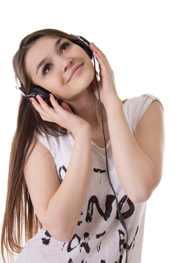 Het blije tienermeisje met hoofdtelefoons luistert aan de muziek stock afbeelding