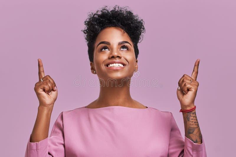 Het blije vrij Afrikaanse Amerikaanse wijfje wijst op met beide voor omhoog vingers, heeft vriendschappelijke glimlach, donkere h royalty-vrije stock foto's