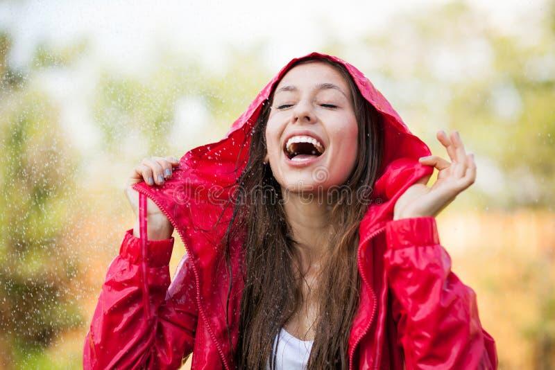 Het blije vrouw spelen in regen stock afbeelding