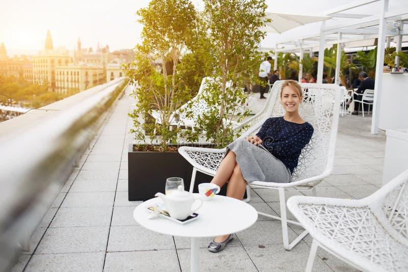 Het blije wijfje geniet in het buitenland van haar recreatietijd in koffiewinkel tijdens reis royalty-vrije stock foto's