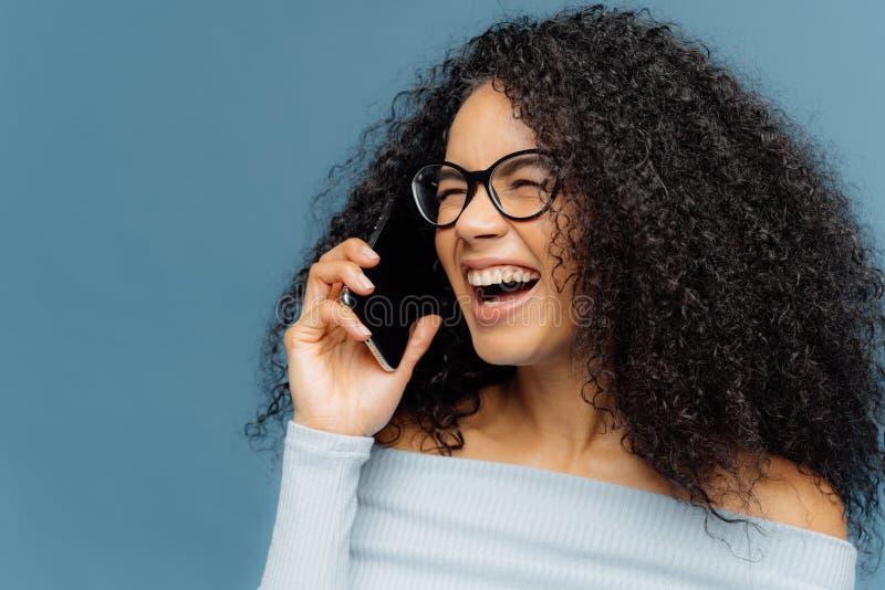 Het blije wijfje heeft Afro-haar, gelukkig lacht, spreekt via cellulair, bespreekt grappig iets met vriend, ruim glimlacht, toont royalty-vrije stock foto's