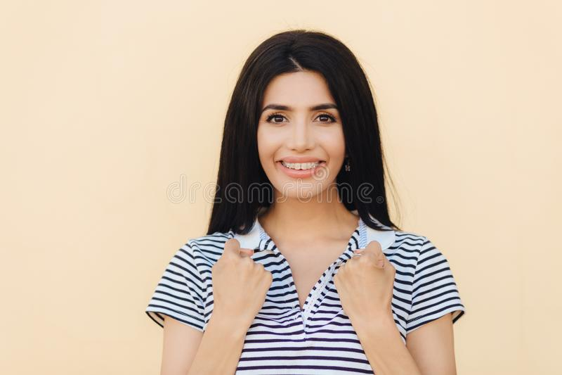 Het blije wijfje met prettige glimlach, houdt indient vuisten, draagt steunen op tanden, heeft donker recht die haar, over beige  stock foto