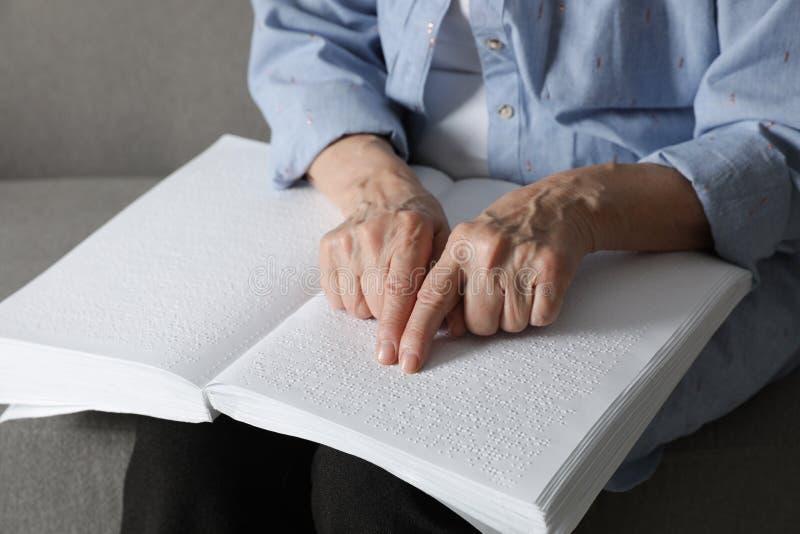 Het blinde hogere die boek van de persoonslezing in Braille op bank wordt geschreven stock afbeeldingen