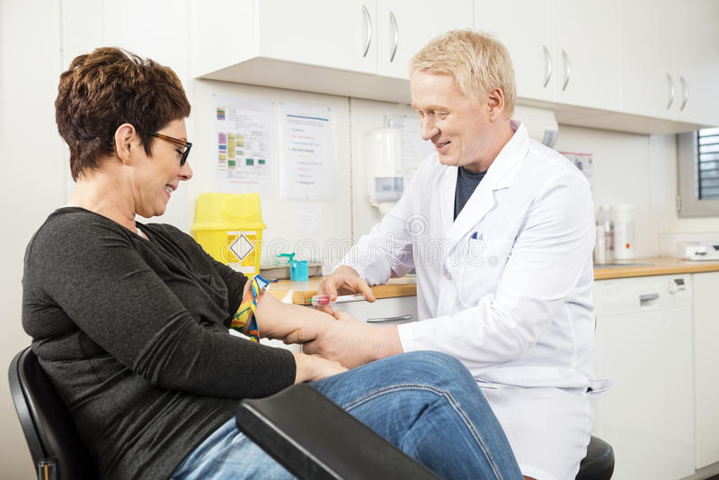 Het Bloed van mannelijke Artsencollecting patient voor Test royalty-vrije stock afbeeldingen