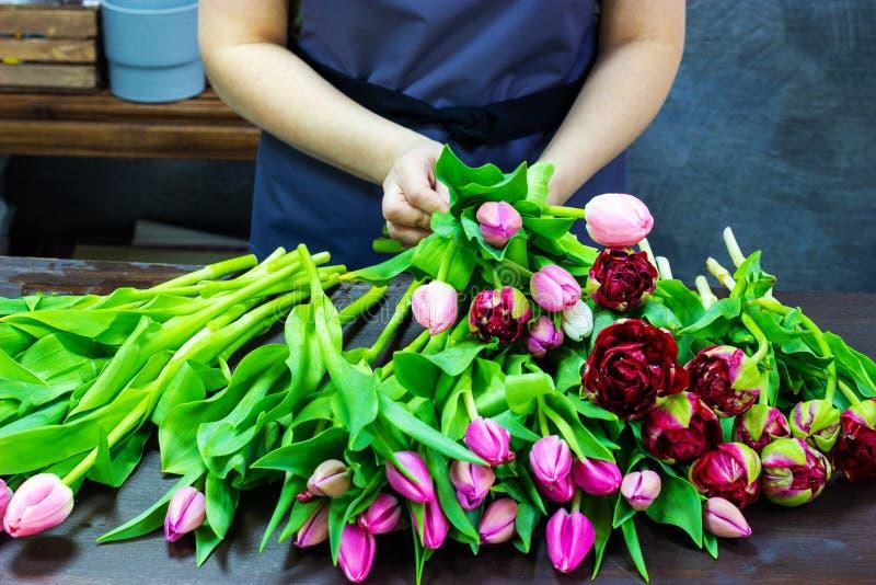 Het bloemistmeisje maakt een boeket van tulpen stock foto