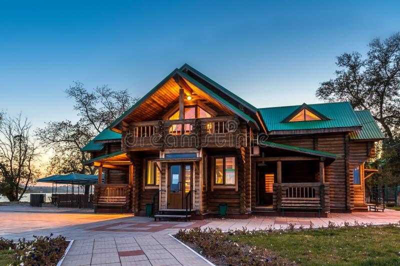 Het blokhuis van het land met verlichting en groen dak op de achtergrond van de avond blauwe hemel royalty-vrije stock foto's