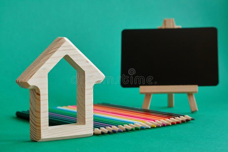 Het blokhuisbeeldje, het miniatuurschoolbord op een schildersezel en de kleurenpotloden die door regenboogkleuren worden opgemaak stock afbeeldingen
