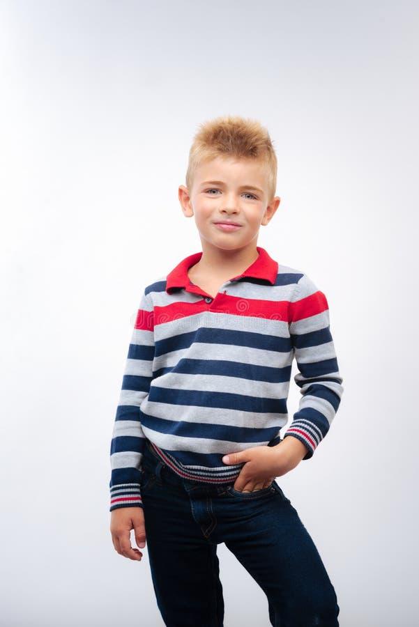 Het blond weinig jongen dient stellen met zak in stock foto
