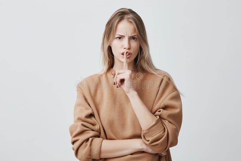 Het blonde het aantrekkelijke Europese wijfje camera bekijkt houdt vinger op lippen die, en vraagt om lawaai niet te maken zijn n royalty-vrije stock foto's