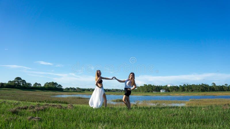 Het blonde & het brunette die van de twee vrouwenvriend een hart met handen maken voor valentijnskaartendag royalty-vrije stock fotografie