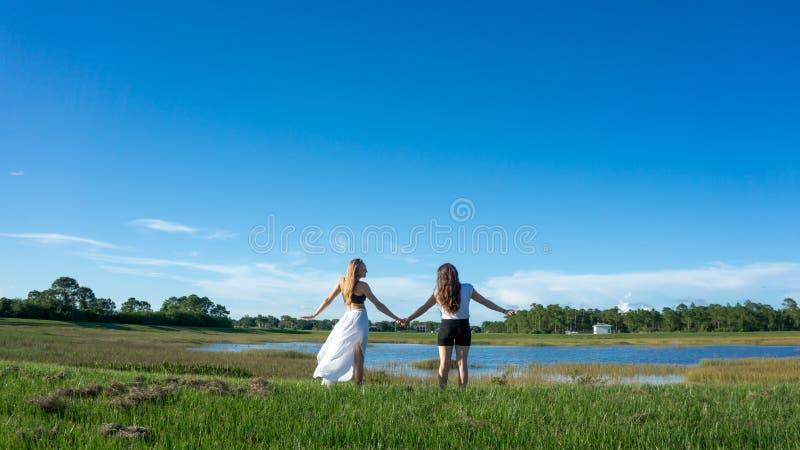 Het blonde & het brunette van de twee vrouwenvriend met lange haarholding dienen een gebied naast een meer in Florida in stock foto