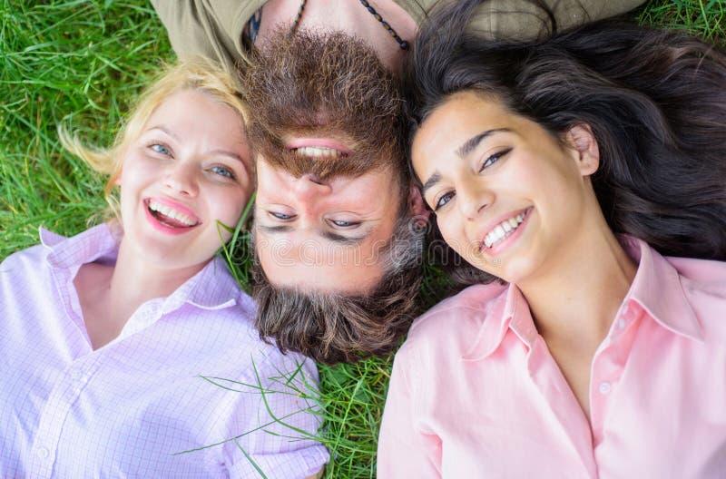 Het blonde en het brunette leggen op zijn schouders Man daling van liefde beide vrouwen Hipster die prettig vrouwenbedrijf ontspa royalty-vrije stock foto's