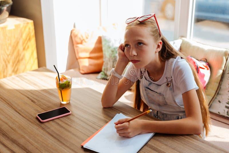 Het blonde-haired tienergevoel bored terwijl het doen van thuiswerk stock foto