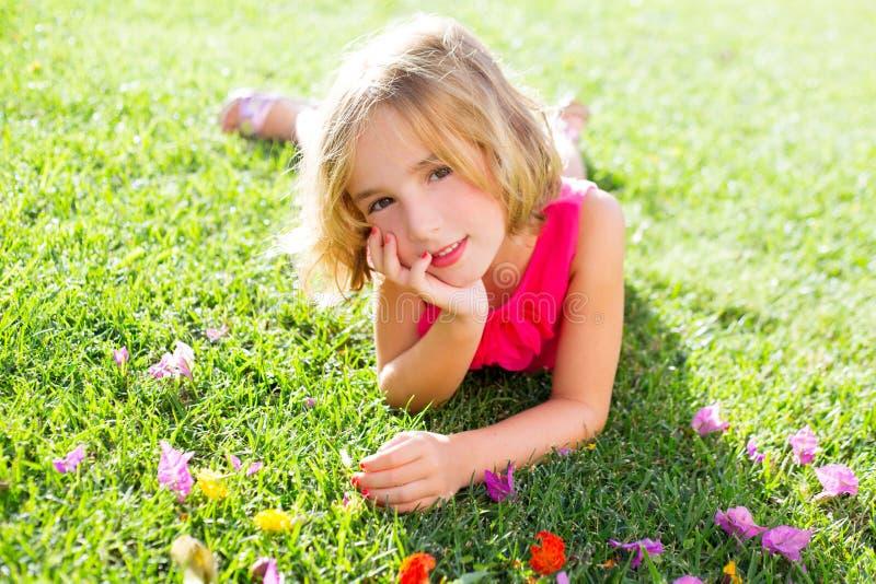 Het blonde jong geitjemeisje ontspannen liggen in tuingras met bloemen stock foto's