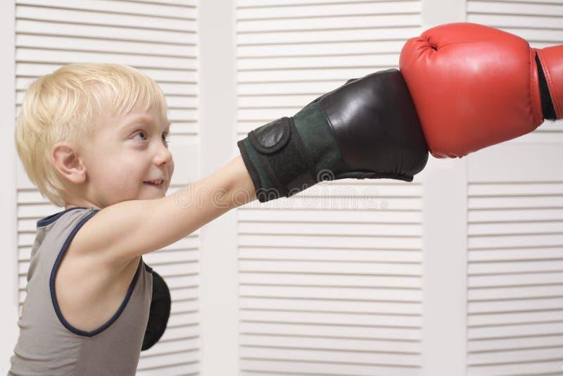 Het blonde jongen in dozen doen met dient rode handschoen in emoties royalty-vrije stock foto