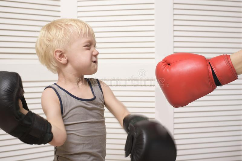 Het blonde jongen in dozen doen met dient rode handschoen in emoties stock afbeeldingen