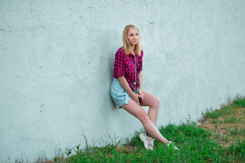 Het blonde in lichtblauwe high-rise borrels, rood plaidoverhemd, stelt op een blauwe muur als achtergrond op de straat, die tegen stock foto's