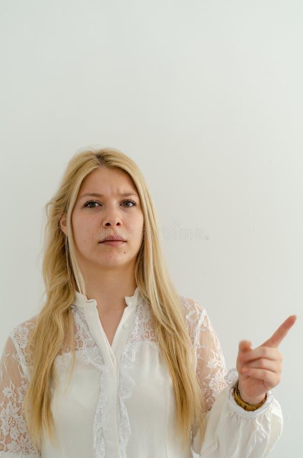 Het blonde meisje fronst wenkbrauwen en heft haar wijsvinger het richten op stock foto