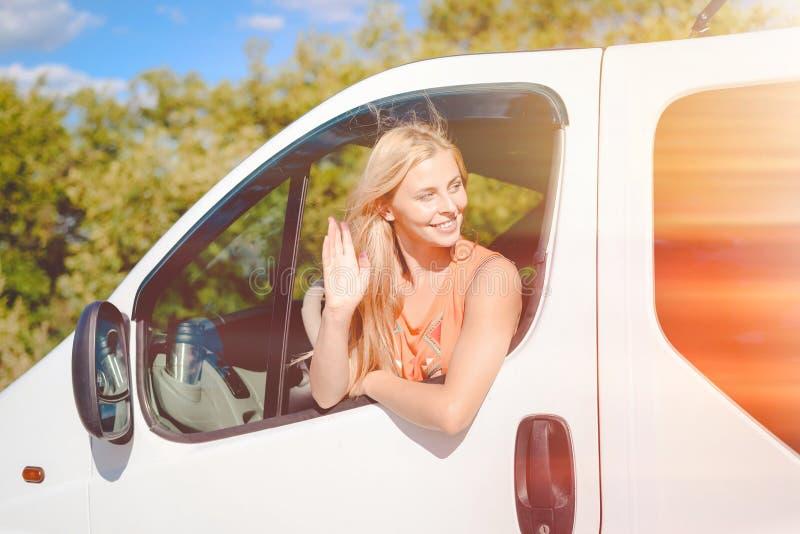 Het blonde meisje gelukkige glimlachen van en het begroeten van iemand van royalty-vrije stock foto