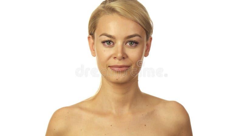 Het blonde meisje kijkt neer en bekijkt dan omhoog de camera en glimlacht royalty-vrije stock fotografie