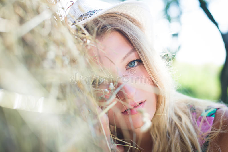 Het blonde meisje ligt op hooiberg in zonnige de zomer stock foto's