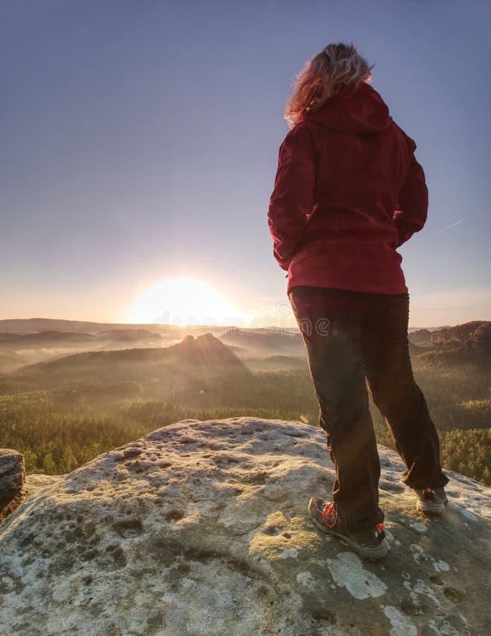 Het blonde meisje met dient jasjezakken in wandelend in bergen stock foto
