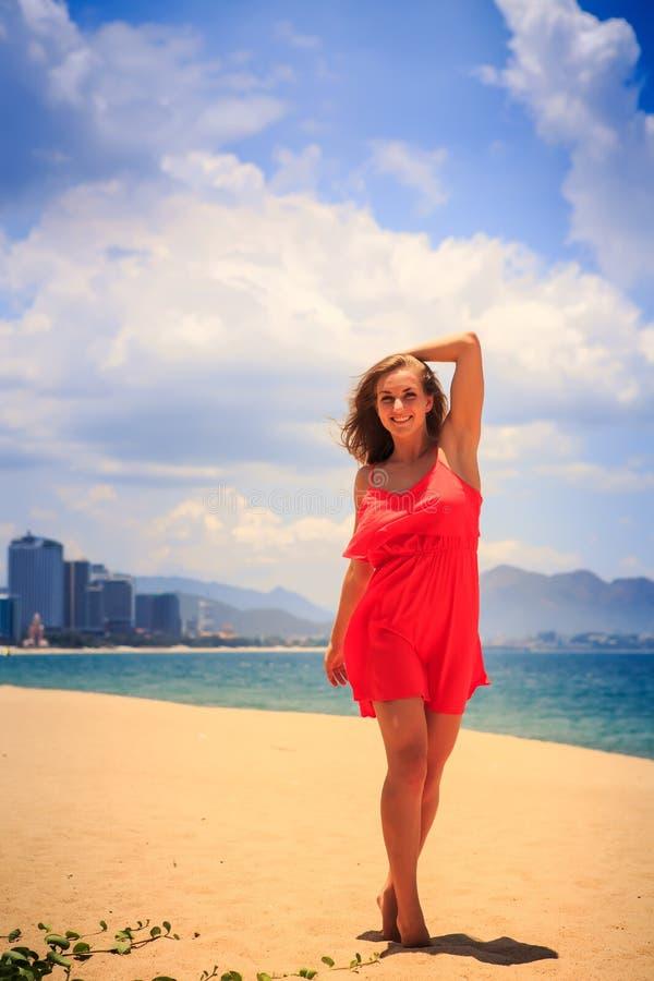 het blonde meisje in rode tribunes op strand maakt geschud door windhaar glad stock fotografie