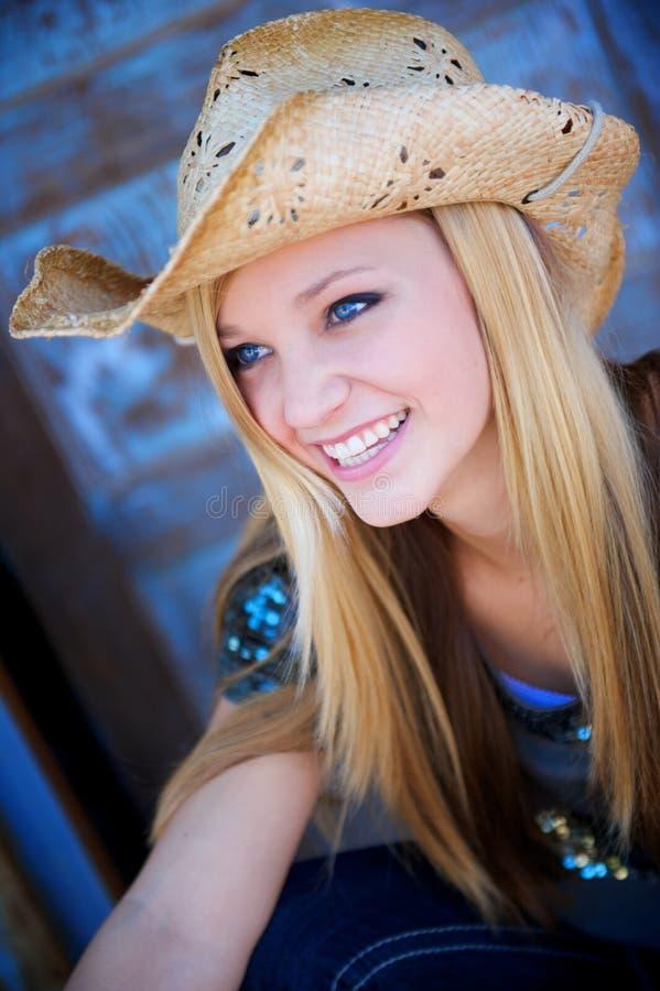 Het blonde Model glimlacht terwijl het Dragen van de Hoed van de Cowboy stock fotografie