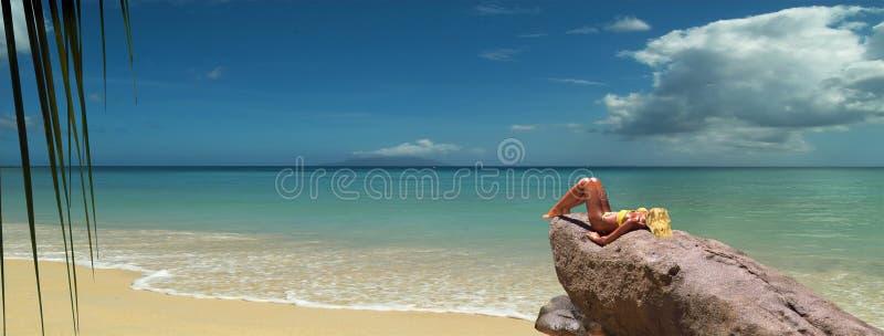 Het blonde model tunning op strandrots. Panorama royalty-vrije stock afbeeldingen