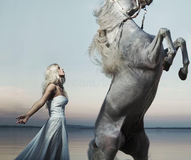 Het blonde nimf stellen met majestueus paard royalty-vrije stock foto's