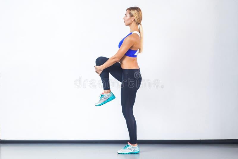 Het blonde sportieve vrouw van de Rofilemening, die op één been in evenwicht brengen stock foto's