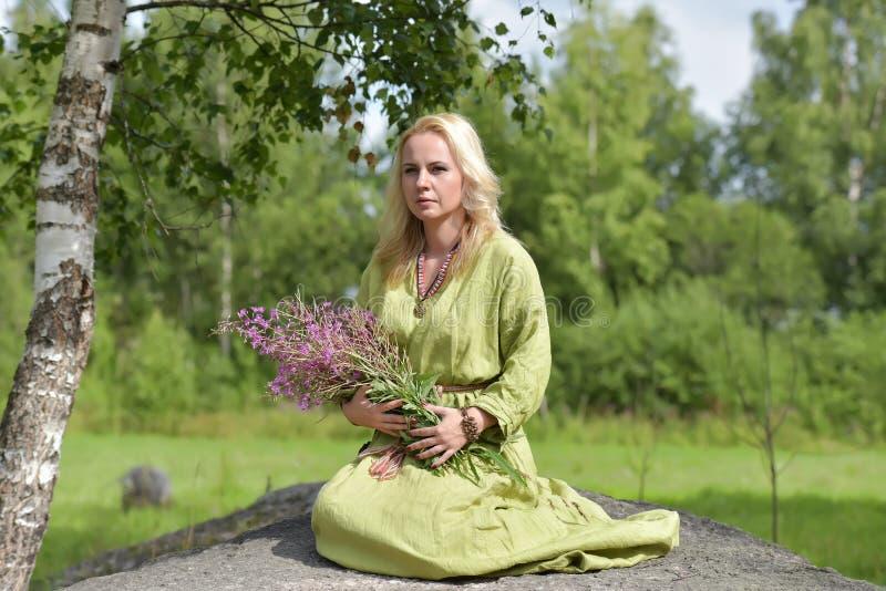Het blonde in uitstekende kleren van Viking zit met wilde bloemen i stock afbeeldingen