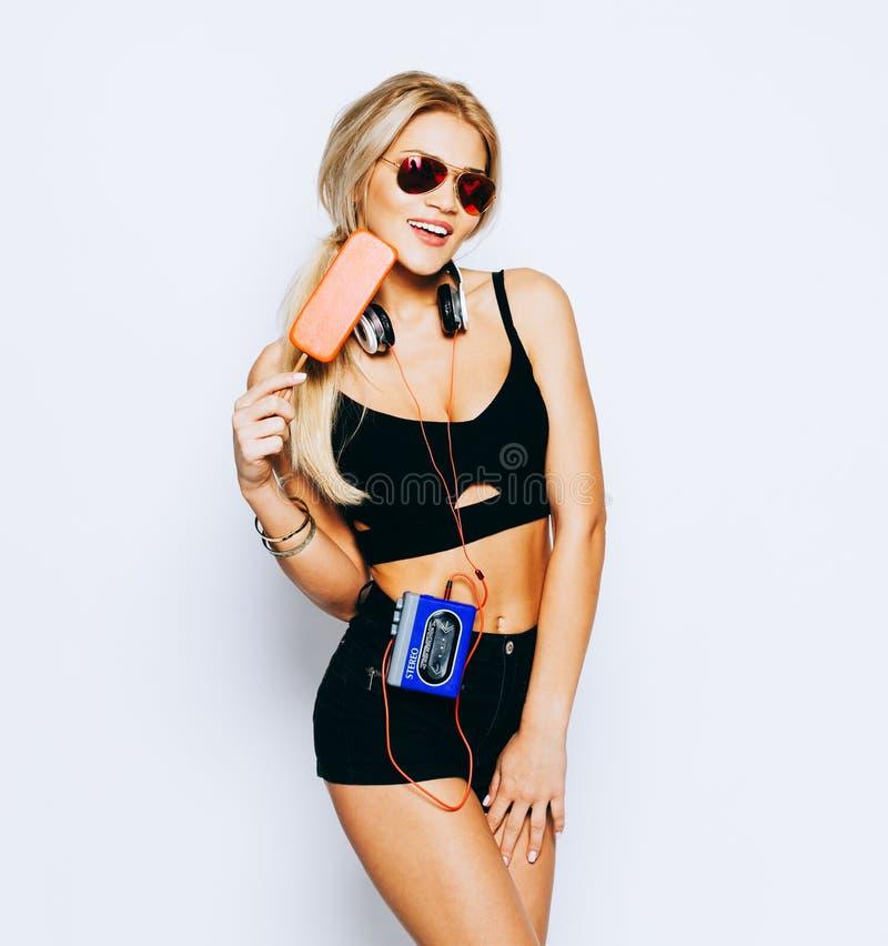 Het blonde van het Breathtakingly het mooie meisje stellen in een zwarte uitrusting, zonnebril met een roomijsroomijs en een wijn royalty-vrije stock foto